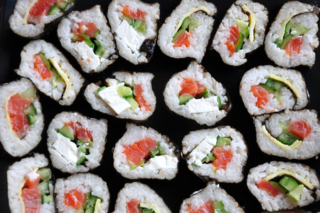 Homemade rolls made of rice, salmon, cheese and cucumber closeup. Sushi  texture.
