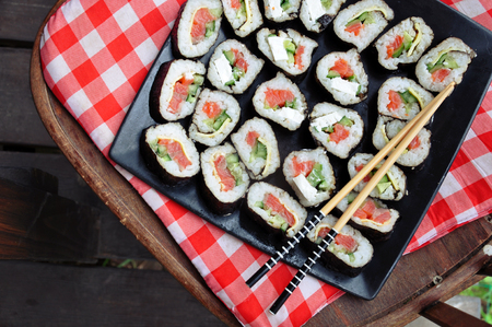 Sushi on a black square dish with chopsticks on a checkered red cloth, top view. Lizenzfreie Bilder