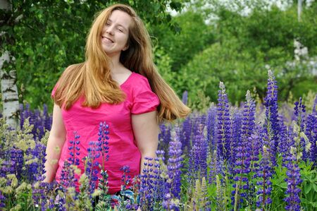 Portrait of smiling young European red-haired girl in a pink blouse in a field of blooming lupines.