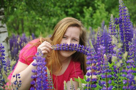 Portrait of smiling young European red-haired girl in a pink blouse in a field of blooming lupines, making mustache of flowers.