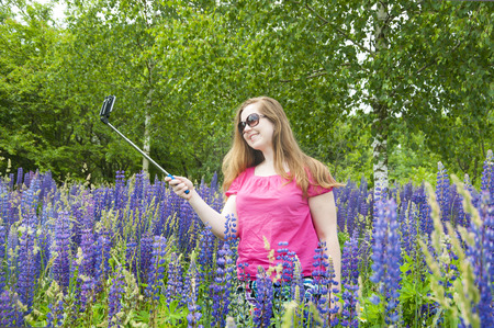 Young European red-haired girl in a pink blouse photographed themselves on selfie stick in a field of blooming lupines. Lizenzfreie Bilder