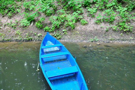 Blue wooden boat on the river bank.
