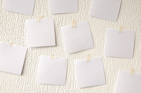 Many square paper stickers on a white plaster wall.