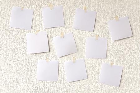 Many square paper stickers on a white plaster wall. Lizenzfreie Bilder