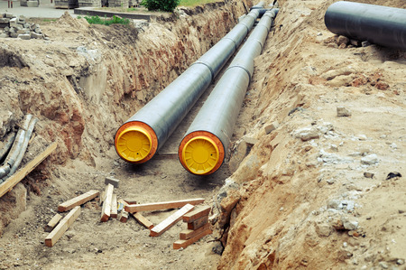 The process of laying of engineering heating systems. Two black plastic pipes with yellow bases in sandy trench in perspective.