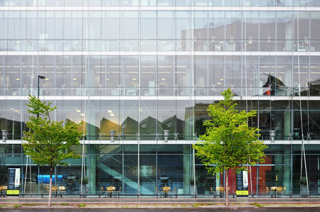 Berlin, Germany - April 12, 2017: Multistory glass office building and green trees in the foreground. Editorial