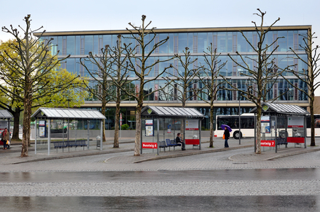 Ravensburg, Baden-Wuerttemberg, Germany - April 23, 2017: Public transport stops and bare trees against the Ravensburg glass industrial building.