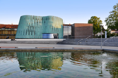 Fellbach, Baden-Wurttemberg, Germany - April 20, 2017: The modern building of the music school in Fellbach reflected in artificial pond.