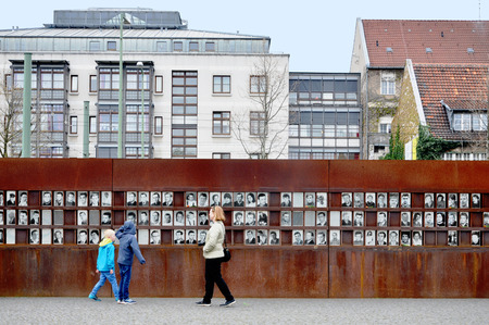 Berlin, Germany - April 12, 2017: Monument of the Berlin Wall with photos of people and visitors. Editorial