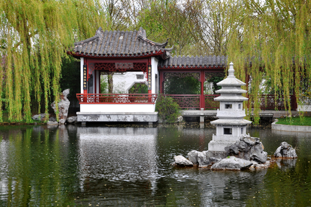 Berlin, Germany - April 13, 2017: Pagoda by the lake in the Chinese Garden  in Gardens of The World  in Berlin.