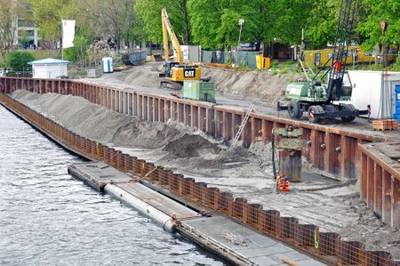 Berlin, Germany - April 15, 2017: The process of construction of the embankment. Installation of metal formwork and mound. Excavators in the background. Sajtókép