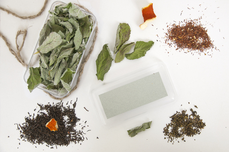 Mock up of box with mint and melissa, green and black tea, dried orange peel on white background. Top view.