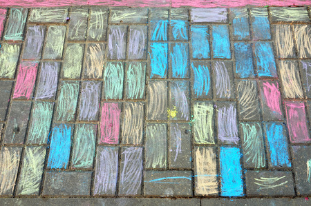 Concrete paving tiles painted with colored crayons. Look down.