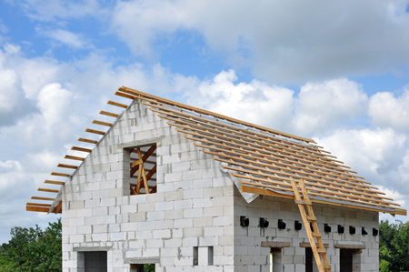 The process of building a private house of cellular concrete blocks and installing a wooden roof truss system. Stock Photo