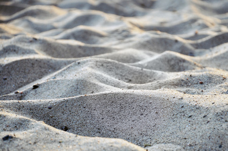 Texture of waves of gray sand. Selective focus.
