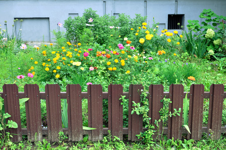 Small brown fence separating the flower bed.