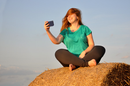 Happy red-haired girl sits on a haystack and makes selfie on the phone. Lizenzfreie Bilder