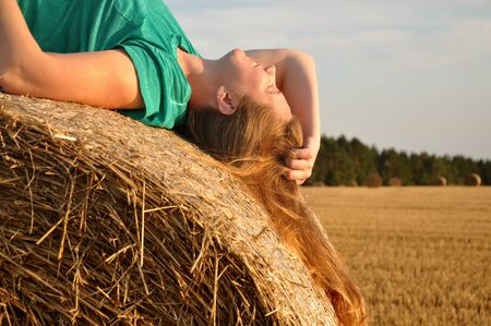 Happy red-haired girl is resting on a haystack. Profile view.