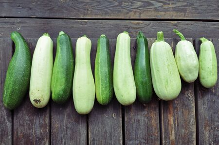 Many ripe squash and zucchini on a brown wooden surface top view. Lizenzfreie Bilder