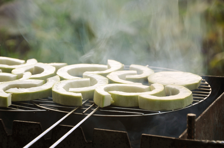 Semicircular pieces of raw white squash roasted on the grill.