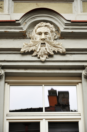 Decorative sculpture of the old mans head above the window. Vilnius, Lithuania. Lizenzfreie Bilder