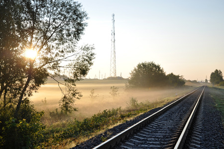 The railway in the fog on a sunny morning.  The sun rays penetrate through the trees. Lizenzfreie Bilder