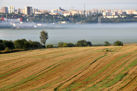 Agricultural field after harvest in the foreground. Morning city covered with fog in the background. Grodno, Belarus. Lizenzfreie Bilder
