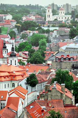 Fragment of the old town Vilnius panorama with red roofs and towers of churches. Lithuania. Vertical view.