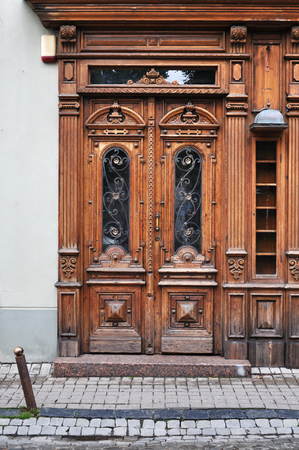 Brown vintage wooden door with carver decor. Vilnius, Lithuania. Lizenzfreie Bilder