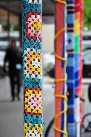 A street pole, tied with colored woolen threads. Close up. Selective focus.