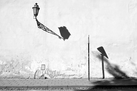 The wall of the white building with contrasting shadows of street lamp. Black and white composition.