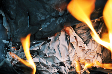 Stack of burnt paper and  fire. Close-up, selective focus.