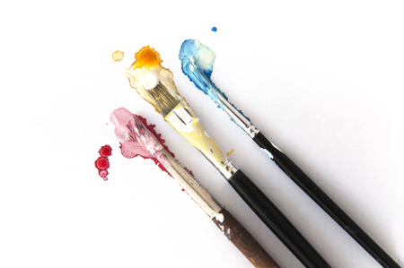 Three brushes in Cyan, Magenta, Yellow paint on white background. CMYK concept.