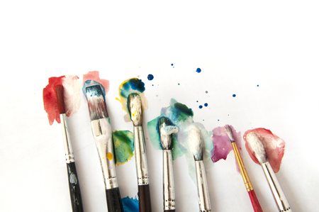 Many brushes in color paint on a white background. Lizenzfreie Bilder
