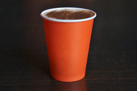 Red paper cup of coffee on a dark brown background. Empty space for text.