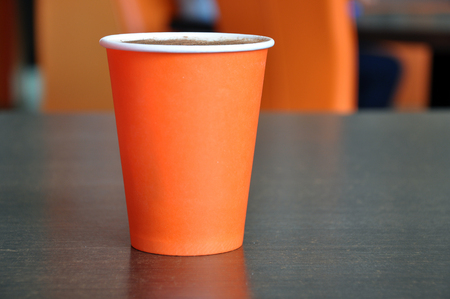Red paper cup of coffee on a table in the blurred background of a cafe. Empty space for text. Lizenzfreie Bilder