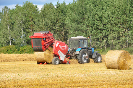 The tractor twists round haystacks in the agricultural field. Editorial
