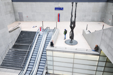 Entrance to the modern underground metro station in Berlin. White hall with stairs and escalator.