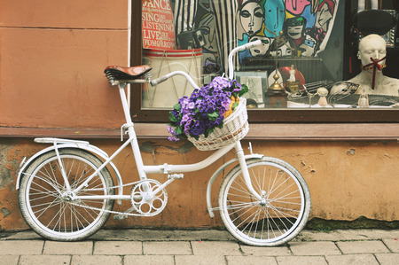 A white vintage bicycle with a basket full of blue flowers and a street in Vilnius.