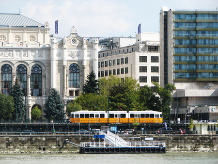 The Danube embankment in Budapest with historical buildings and a riding yellow tram. Front view. Hungary. Editorial