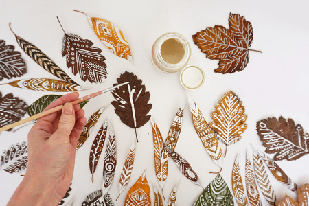 The process of painting on leaves. Many autumn dry leaves with ethnic patterns, hand with a brush and a gouache can, top view. Stock Photo
