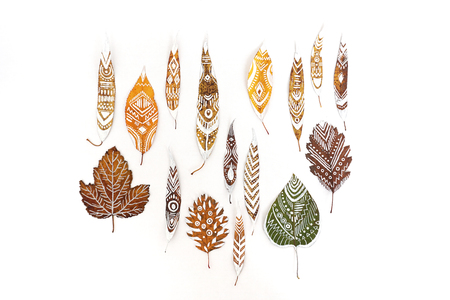 A lot of autumn dry leaves with white hand-drawn ethnic patterns. Isolated. Top view. Standard-Bild