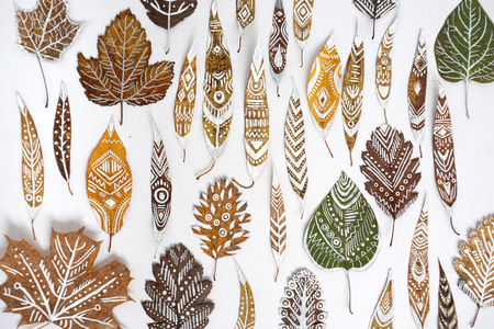 A lot of autumn dry leaves with white hand-drawn ethnic patterns.