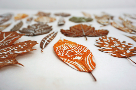 A lot of autumn dry leaves with white hand-drawn ethnic patterns. Selective focus.