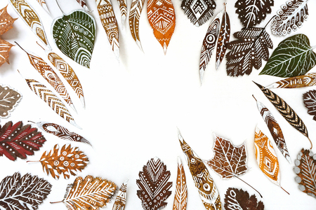 Frame made of autumn dry leaves with white hand-drawn ethnic patterns. Empty space. Standard-Bild