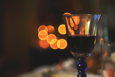 A glass of red wine on the background of Christmas lights in bokeh.