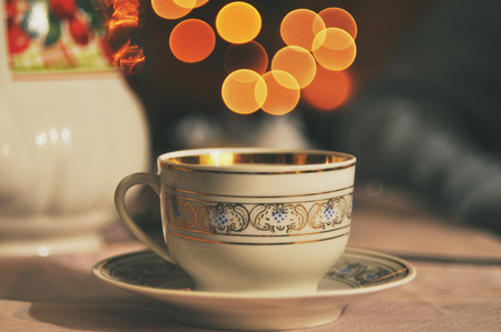 Vintage porcelain cup on the background of yellow Christmas lights in bokeh. Standard-Bild