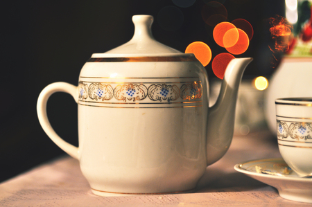Vintage porcelain teapot on the background of Christmas lights in bokeh.