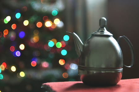 Metal teapot on background Christmas lights in bokeh.