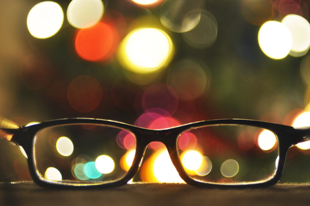 Glasses in a black frame close-up on a background of Christmas lights in bokeh. Place for text.